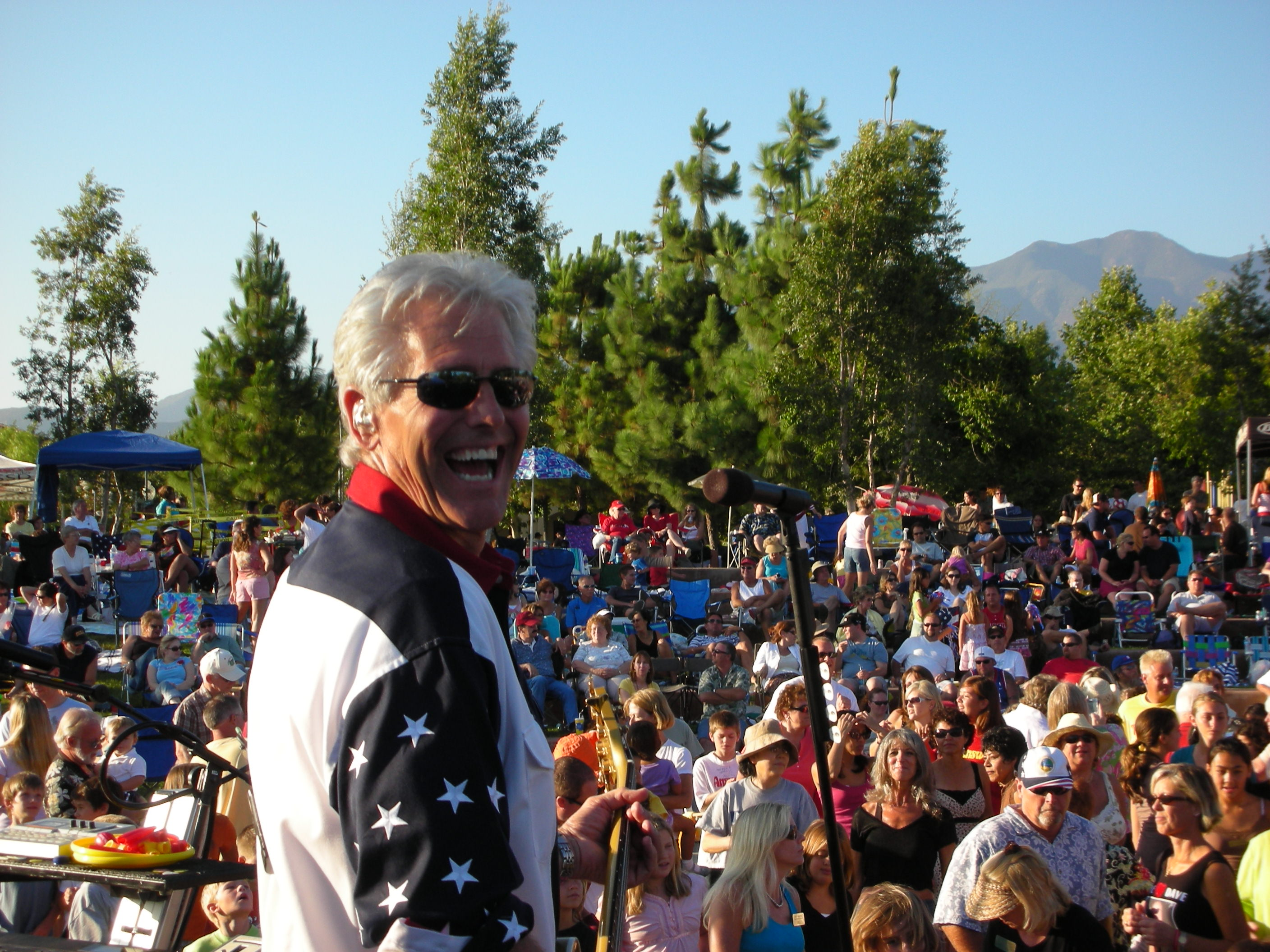 Man in American jacket smiling during outdoor concert